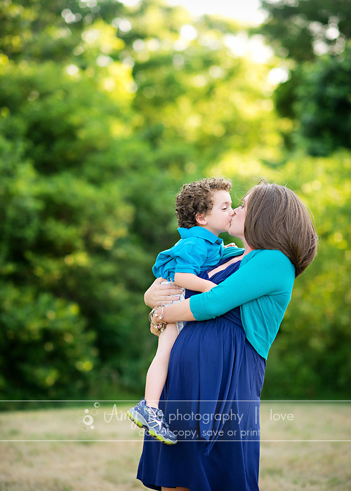 Mom Kissing Son During Maternity Session Lifestyle Backyard Blue And Green Massachusetts