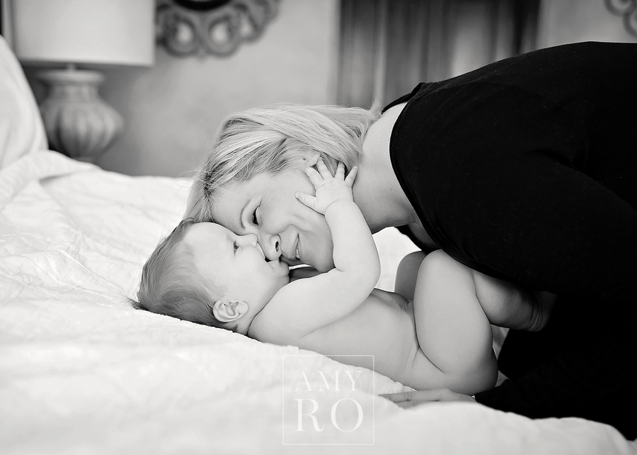 Black and white image of mom and baby snuggling on bed