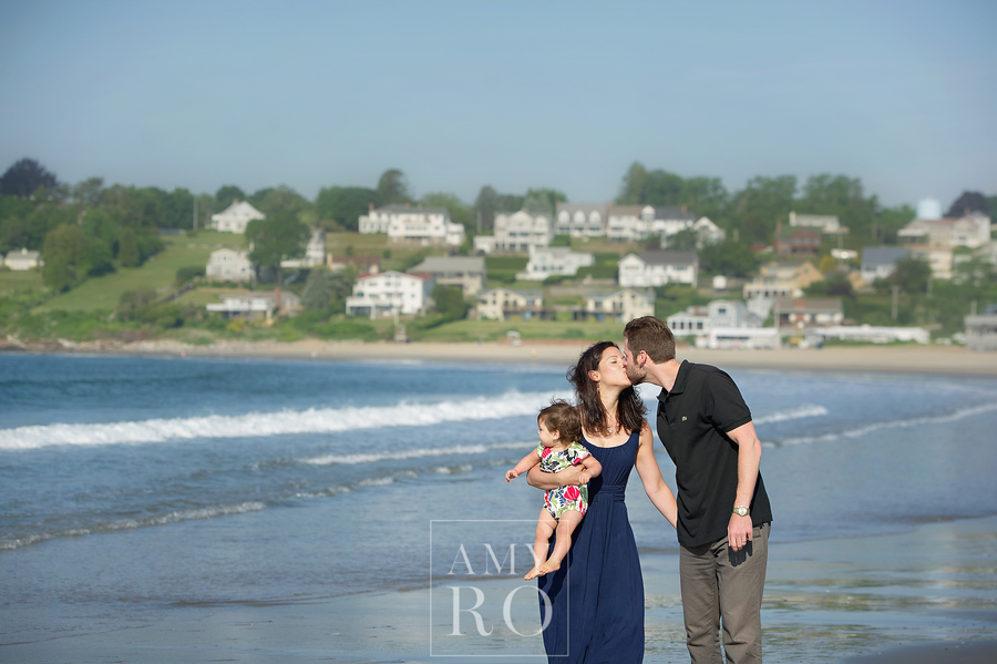 Color image of couple walking on beach with baby daughter kissing taken during family session at Bonnet Shores in Narragansett