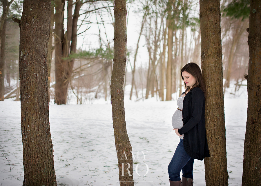 Maternity session in the snow leaning against a tree