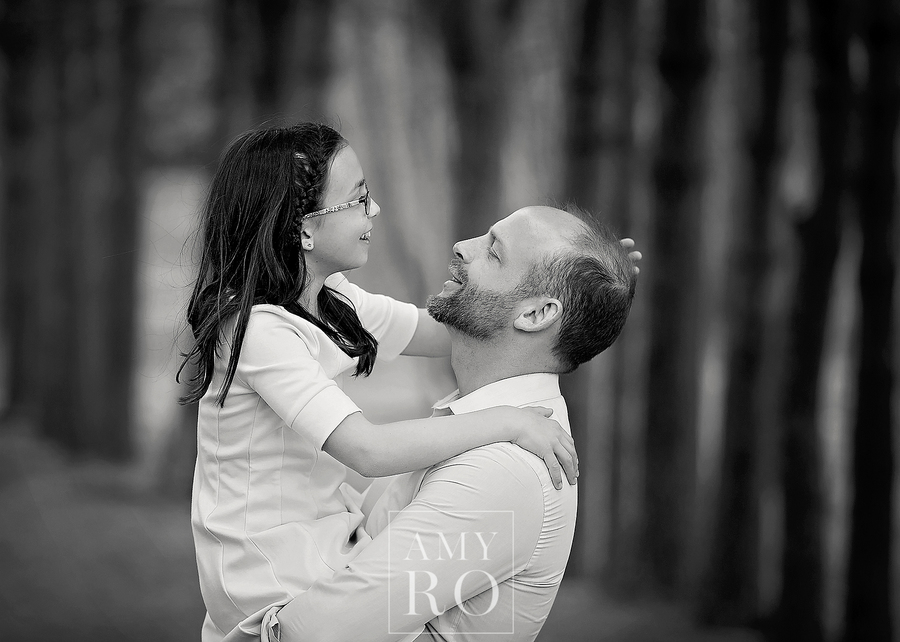 Black and white image of dad holding his older daughter laughing in the woods