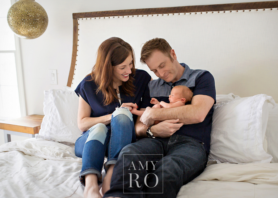 Image of mom and dad with newborn  snuggling on their restoration hardware bed  during an in-home lifestyle newborn session in East Greenwich